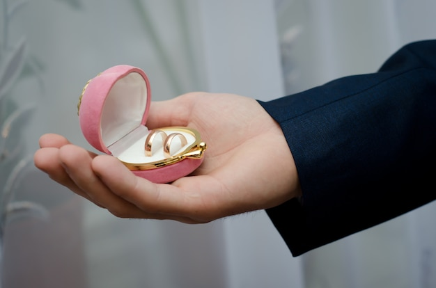Doos met trouwringen in de hand van de bruidegom