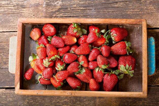 Doos met verse aardbeien op een houten tafel