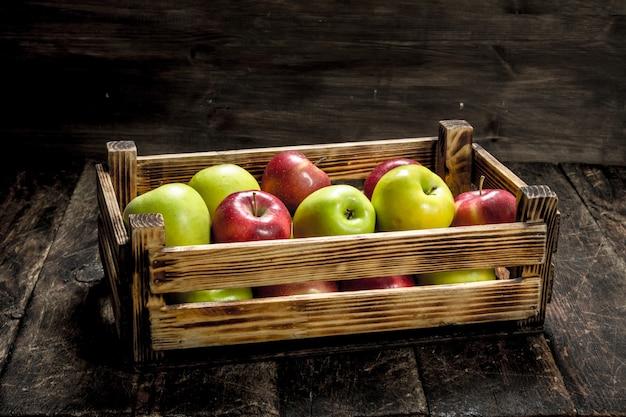Doos met verse rode en groene appels. op een houten achtergrond.