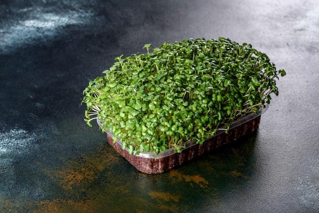 Doos met verse spruiten van micro-radijsgroenten voor het toevoegen van gezonde voeding aan gerechten. vegitaire gerechten bereiden