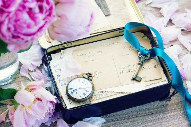 Doos met vintage post, oude sleutel en antieke klok