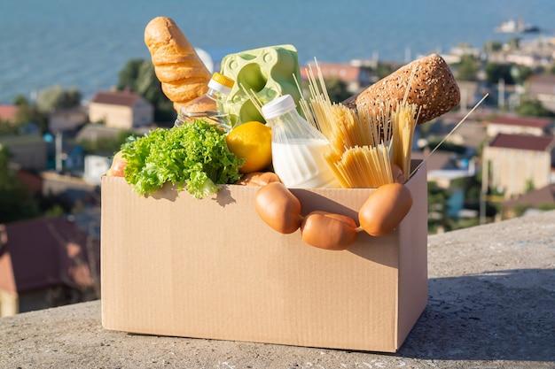 Doos met voedsel liefdadigheidsdonatie, contactloze bezorging van boodschappen tijdens quarantaineconcept