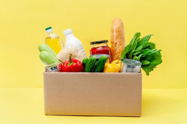 Doos met voedselvoorraden. essentiële goederen: olie, ingeblikt voedsel, granen, melk, groenten, fruit