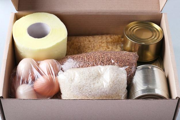 Doos met voedselvoorraden op lichtblauwe achtergrond. rijst, boekweit, pasta, ingeblikt voedsel