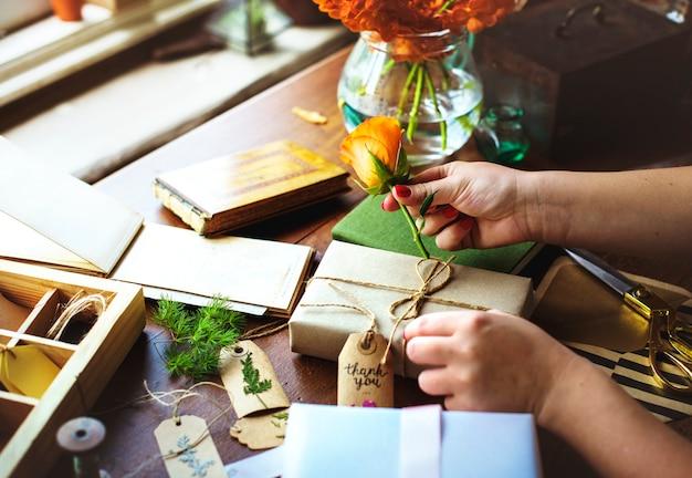 Doos van de handen de diy verpakkende gift op houten lijst