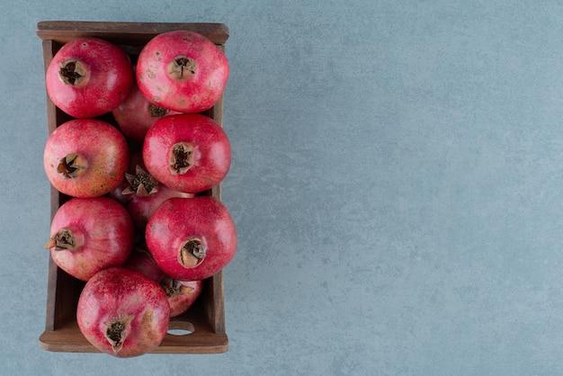 Doos van rijpe granaatappels op marmer.