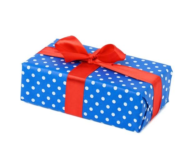 Doos verpakt in blauw polka dot papier en vastgebonden met een rood zijden lint op een witte achtergrond, feest