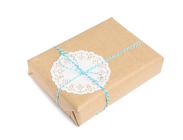 Doos verpakt in bruin kraftpapier en vastgebonden met blauw touw, cadeau geïsoleerd op een wit oppervlak