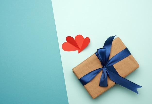 Doos verpakt in bruin papier en gebonden met een blauw zijden lint met een strik, cadeau, bovenaanzicht,