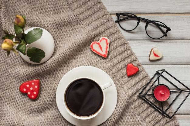 Doosje met een cadeautje voor de valentijnsdagkoekjes in de vorm van een hart en kopjes zwarte koffie