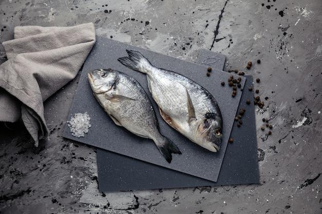 Dorada op een grijs bord en donkere tafel