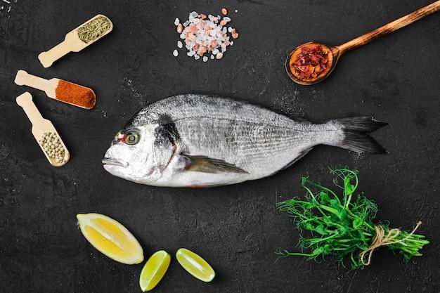 Dorada vis op tafel met specerijen en kruiden