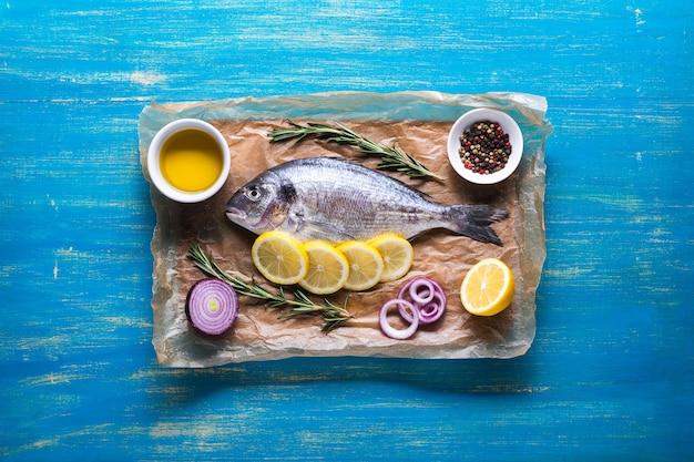 Dorado vis bereid voor het koken op een snijplank en en perkamentpapier met citroen en kruiden. bovenaanzicht op een blauwe houten achtergrond.