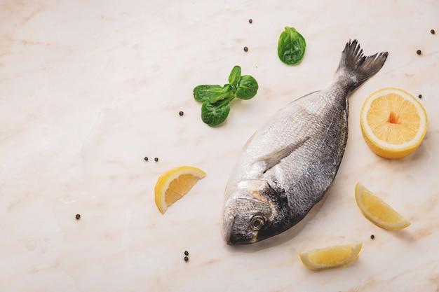Dorado vis, citroen en groene bladeren op marmeren tafel met waterdruppels en zwarte peper