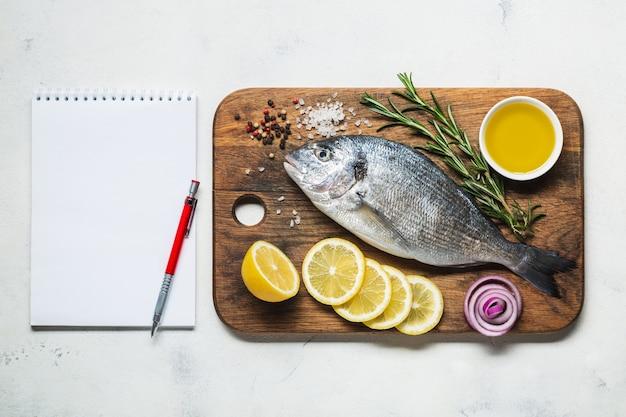 Dorado vis op een rustieke houten snijplank met kruiden en een notitieboekje voor recept of menu. bovenaanzicht op een witte achtergrond.