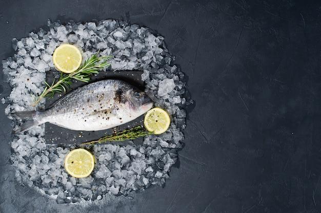 Dorado-vissen ruw op een zwarte hakbord, ingrediëntrozemarijn, citroen, ijs.