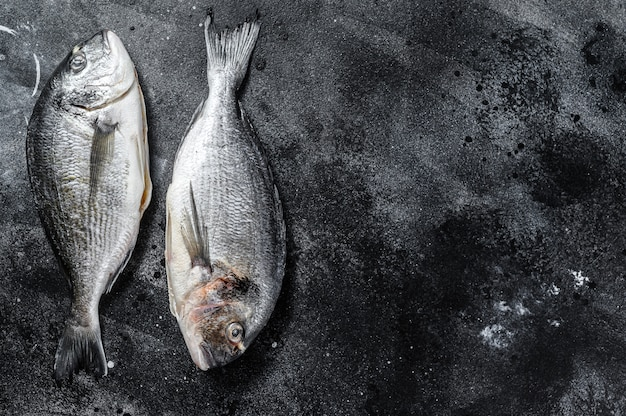 Dorado zeevis. mediterrane keuken, gezond koken concept. zwarte achtergrond. bovenaanzicht. kopieer ruimte