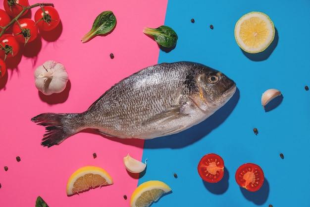 Doradovissen, citroen, knoflook en kerstomaatjes op een helderblauw en roze oppervlak