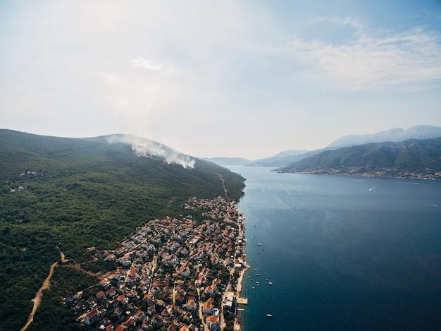 Dorp krasici op het schiereiland lustica in montenegro brandt de bosbrand en rookt de drone