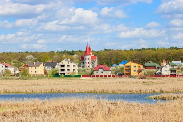 Dorpshuizen aan de rand van een bos op de achtergrond van een meer begroeid met riet