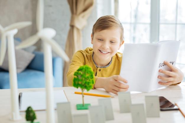 Dorst naar kennis. charmante jonge jongen die een boek over ecologie bestudeert terwijl hij naar de miniaturen van bomen, zonnepanelen en windturbines kijkt