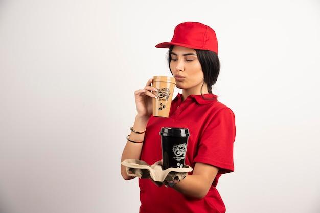 Dorstige koerier die een kopje koffie drinkt. hoge kwaliteit foto