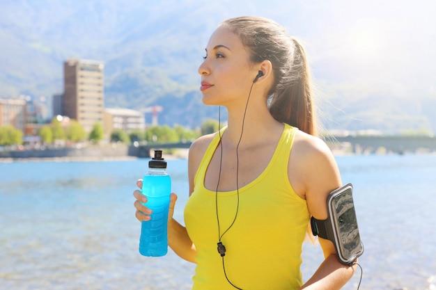 Dorstige vrouwelijke atleet met armband voor slimme telefoon die machtsdrank houdt en buitenshuis wegkijkt.