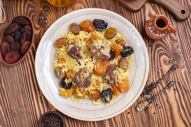Doshama pilaf lamsvlees rijst gemengde droge vruchten ui kastanjes bovenaanzicht