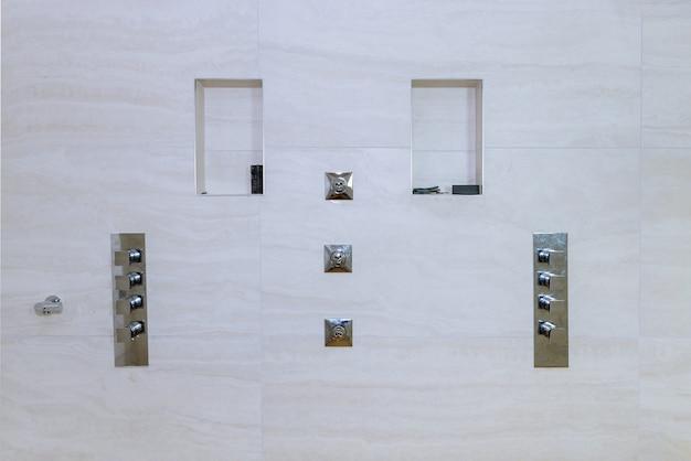 Douche in wederopbouw badkamer wand bedekt betegeld in het nieuwe huis dat in aanbouw is, verbouwing restauratie