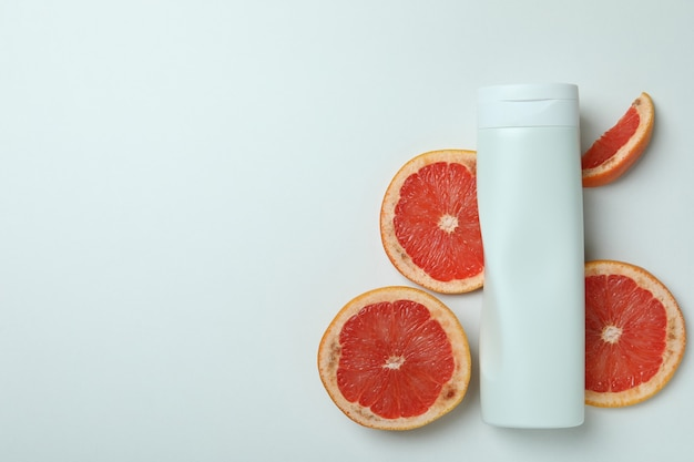 Douchegel en grapefruitplakken op witte achtergrond