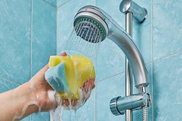 Douchegel schuimt en stroomt naar beneden door de spons voor de badkamer die wordt samengeperst in de menselijke hand die wordt uitgerekt onder de stroming van water dat uit de douchekop stroomt.