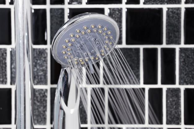 Douchekop in de badkamer met stromende waterdruppels
