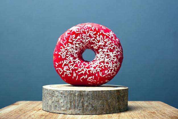 Doughnut met rode glans en wit poeder op een houten tribune op een grijze achtergrond. zoet broodje op een decoratieve bosstandaard.