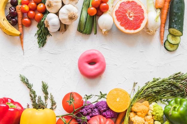 Doughnut tussen het kleurrijke gezonde en ongezonde voedsel op witte geweven achtergrond