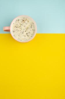 Dovga bovenaanzicht heerlijke greens met oosterse maaltijd in roze beker op de geel-blauwe vloer