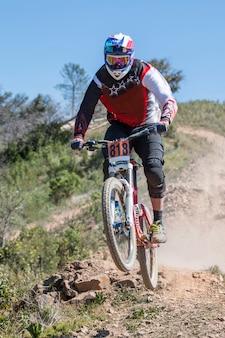Downhill-competitie, biker springt snel op het platteland.