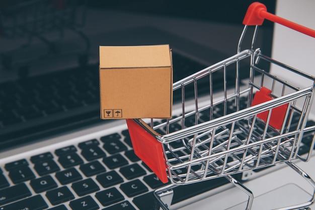 Dozen in en trolley op een laptop online winkelen is een vorm van elektronische handel waarmee consumenten rechtstreeks via internet goederen van een verkoper kunnen kopen.