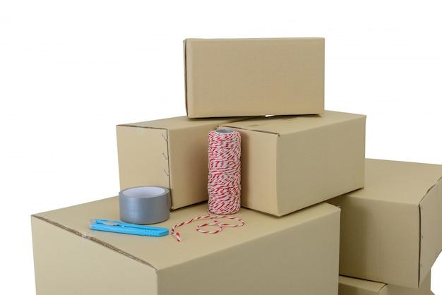 Dozen in verschillende maten gestapelde dozen, plakband, touw en snijder geïsoleerd