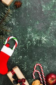 Dozen met geschenken voor kerstmis en verschillende attributen van vakantie op een groene ondergrond. bovenaanzicht, kopie ruimte