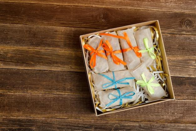 Dozen met verpakte snoepjes. bars. houten tafel. plaats voor tekst
