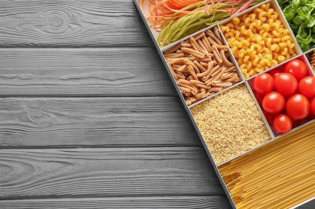 Dozen met verschillende ongekookte pasta en producten op houten