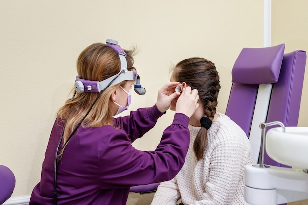 Dr. ent controleert het oor van een meisje in een ziekenhuis met speciale apparatuur