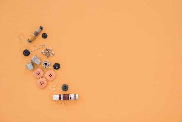 Draad; naald; vingerhoed en verschillende knoppen op gekleurde achtergrond