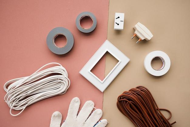 Draad; plug; knop; isolatieband; en handschoen op dubbele achtergrond