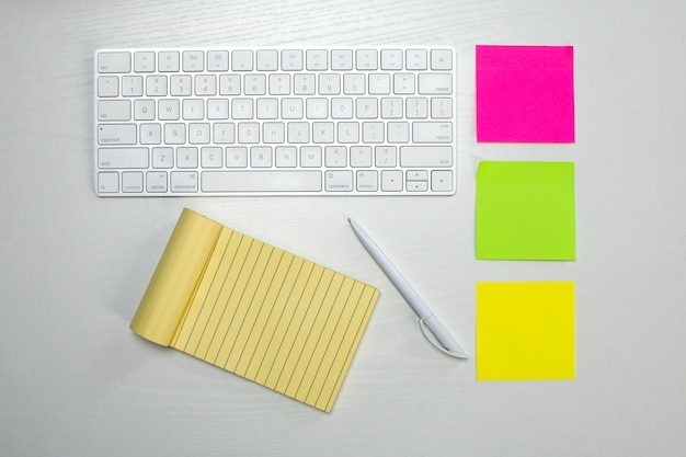 Draadloos toetsenbord en geel notitieblok en plakpapier op tafel