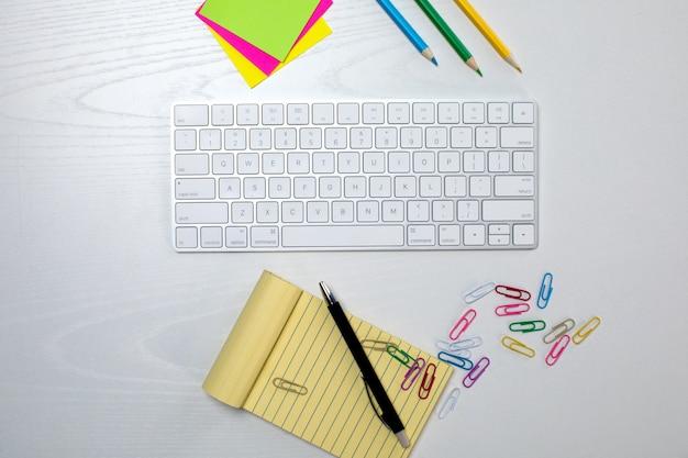 Draadloos toetsenbord en gele kladblok op de tafel