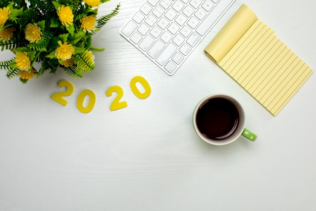 Draadloos toetsenbord notitieblok en kopje koffie