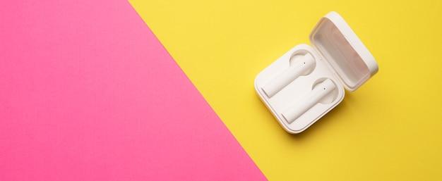Draadloze koptelefoon op een roze en geel oppervlak