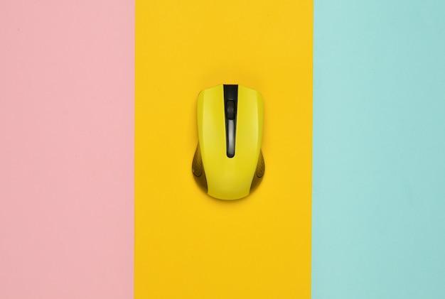 Draadloze muis pc op een veelkleurige papier achtergrond, minimalisme, bovenaanzicht