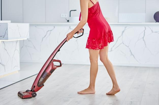 Draadloze rechtop stofzuiger in handen van vrouw in rode peignoir